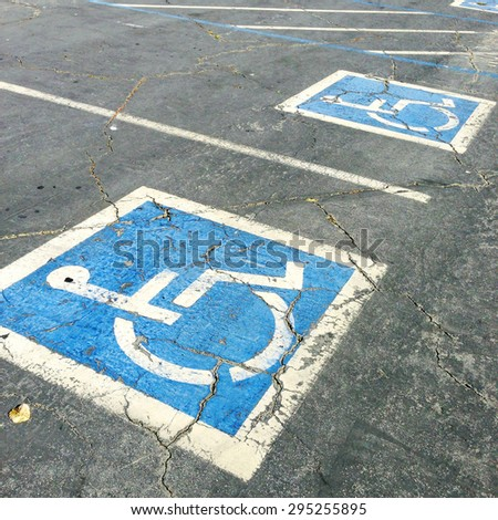 Handicapped symbols painted on parking spaces - stock photo