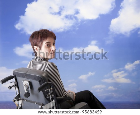 handicapped woman in wheelchair at the beach - stock photo