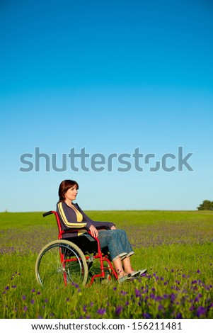 Handicapped woman on a wheelchair over a green meadow  - stock photo