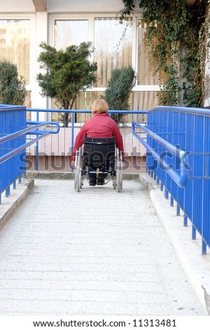 Handicapped woman on wheelchair entering the building using ramp for disabled - stock photo