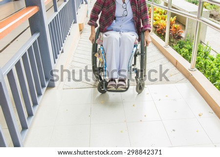 Handicapped woman on wheelchair go to the building using ramp for disabled - stock photo