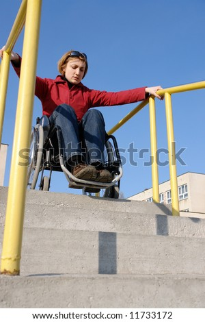 Handicapped woman on wheelchair going down the concrete stairs - stock photo