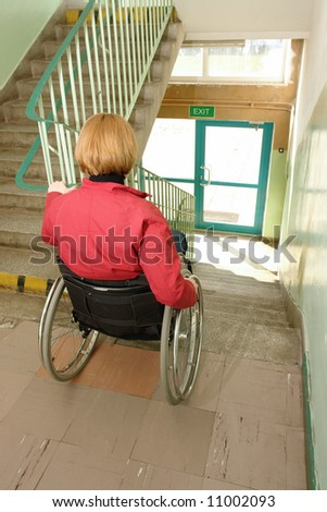 Handicapped woman on wheelchair trying to go downstairs in building staircase - stock photo