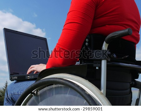 Handicapped woman on wheelchair using laptop outdoors - stock photo