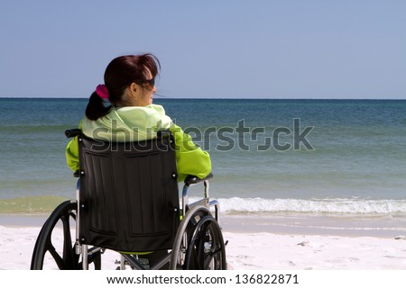 Handicapped woman sits disabled in her wheelchair at the beach. - stock photo