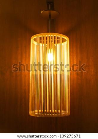 Handicraft electric lamp on wall - stock photo