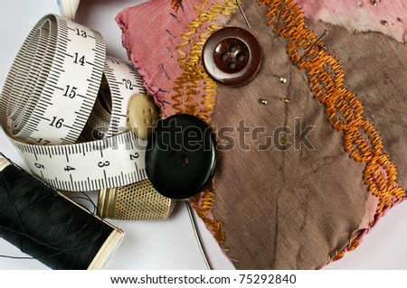 Handicraft fittings like needles, thread, buttons, pincushion and tape measure - stock photo