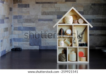 Handicrafts equipment in a wooden house shaped shelf box - stock photo