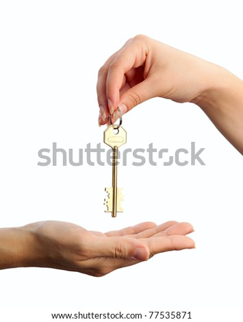 Handing over a key. Female hand holding a key and handing it over to another woman. Concept picture. - stock photo