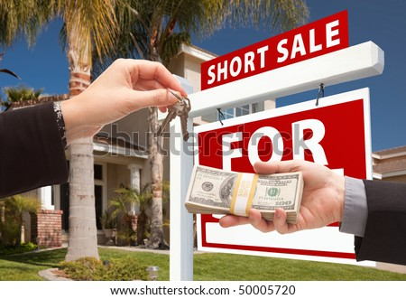 Handing Over Cash For House Keys and Short Sale Real Estate Sign in Front of Home. - stock photo