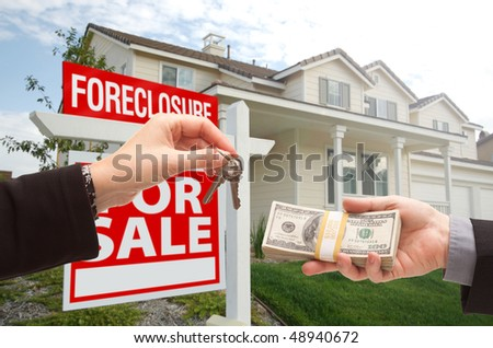 Handing Over Cash For House Keys in Front of House and Foreclosure Sign. - stock photo