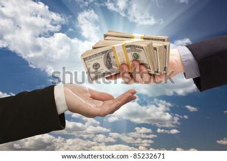 Handing Over Cash with Dramatic Clouds and Sky Background. - stock photo