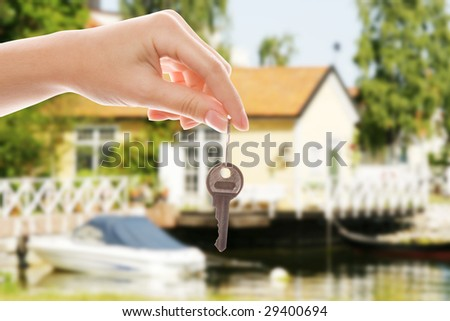 Handing over house key with a new home in the background - stock photo