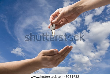 Handing over keys to new owner. On blue sky with clipping path.