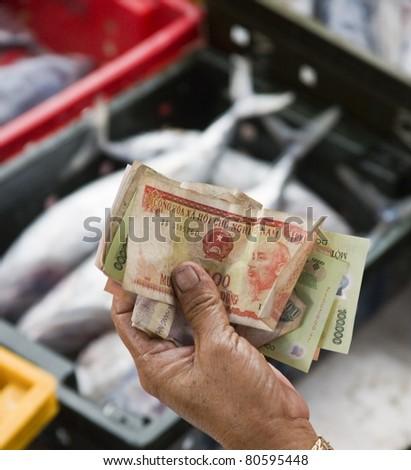 Handing Over Money At A Fish Market, Vietnam - stock photo