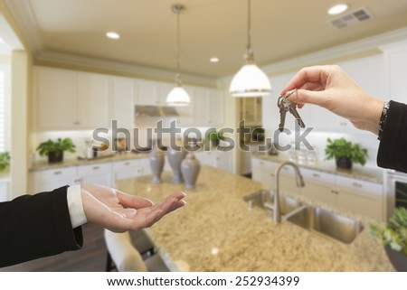 Handing Over New House Keys Inside Beautiful Custom Built Kitchen. - stock photo