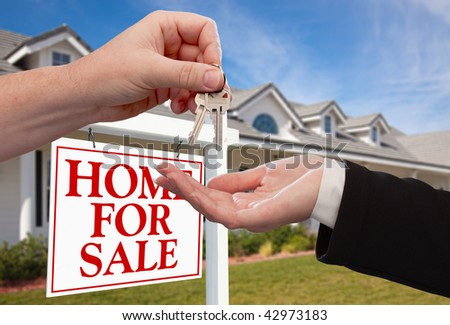 Handing Over the House Keys in Front of a Beautiful New Home. - stock photo