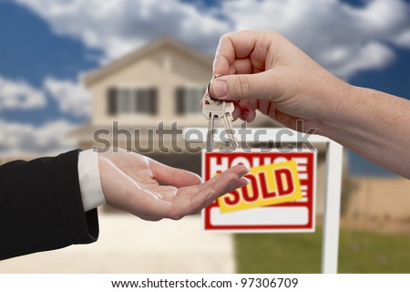 Handing Over the House Keys in Front of Real Estate Sign and Sold New Home. - stock photo