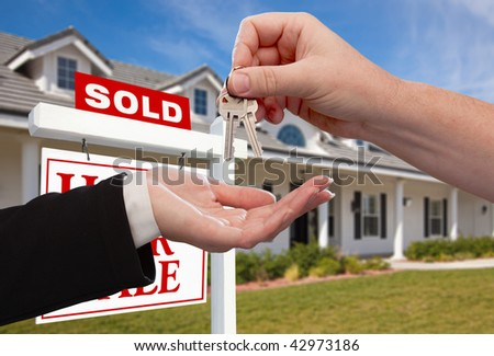 Handing Over the House Keys in Front of Sold New Home Against a Blue Sky - stock photo