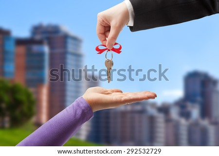 Handing the keys to the new owner on the background of the urban landscape - stock photo