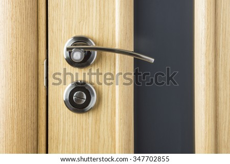 Handle on wooden and glass door close up