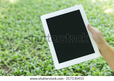 Handle the tablet,view of a woman's hand holding a modern tablet - stock photo