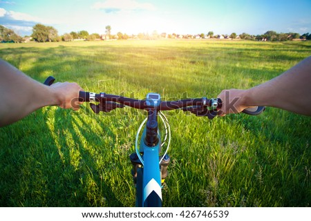 Handlebars with hands of a bicyclist in the field