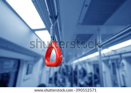 Handles for standing passenger in electric train. - stock photo