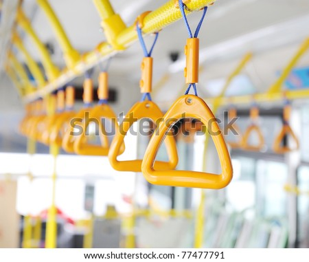 Handles for standing passenger inside a bus. - stock photo