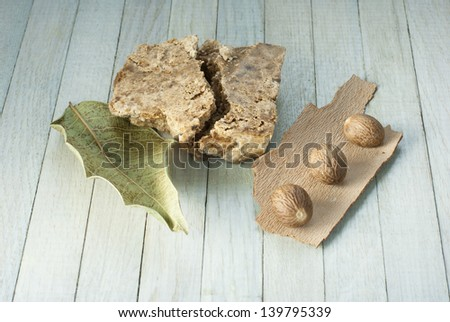 handmade african black soap and ingredients, leaves and shea butter nuts - stock photo