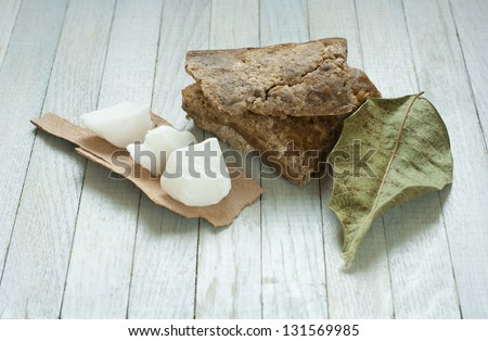 handmade african black soap and ingredients, shea butter leaves and white shea butter - stock photo