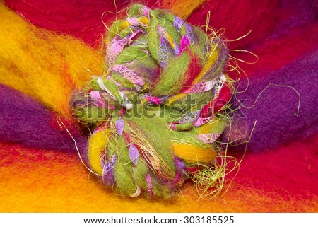 Handmade art yarn from different materials made with a handspindle on a colourful wool felt - stock photo