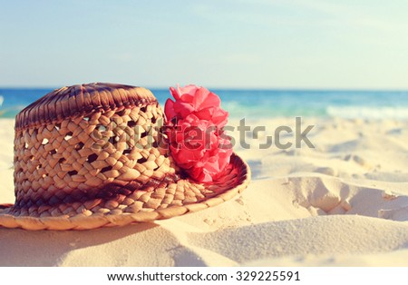Handmade artisan caribbean straw hat and tropical pink flower on white sand, blue sea backdrop. Relaxing beach background. Warm vintage tonality. - stock photo