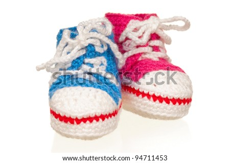 Handmade blue and pink baby booties isolated on white background - stock photo