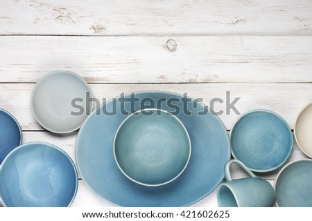 Handmade blue ceramic dish, bowls and mug on rustic white wooden background. Top view point.
