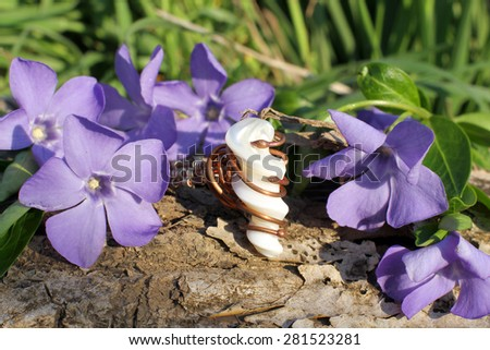 Handmade bronze ring with mother-of-pearl with wood violet in spring on the nature background - stock photo