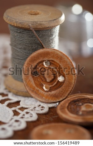handmade button real old reels spool an old thimble and lace backdrop, shallow dof - stock photo