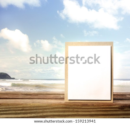 Handmade card on wooden table over blue sky background - stock photo