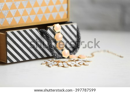 Handmade chest of drawers for jewelry on wooden table background - stock photo