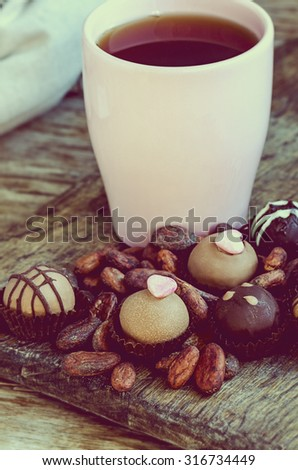 Handmade chocolate candies with cup of tea and cocoa beans served on the vintage wooden table, toned - stock photo
