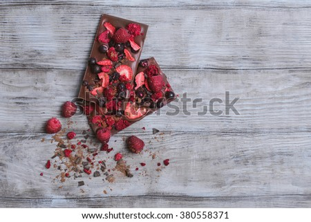 Handmade chocolate with fresh and dried berries, raspberries, strawberries, blackberries, cocoa powder, chips on a light wooden background in rustic style, clean empty place for text, for the recipes - stock photo