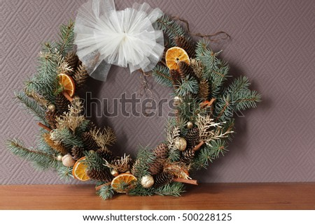 Handmade christmas wreath of grape vines. Decorated with dried orange slices, cones, silver spruce boughs, cinnamon sticks, hazelnuts, walnuts, gold cedar needles and white bow at the top.