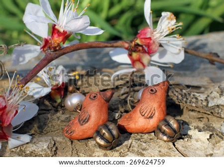 Handmade clay bird earrings with apricot blossom in spring on the nature background - stock photo