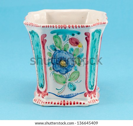 handmade colorful angular clay ceramic vase witf flower ornament on blue background.