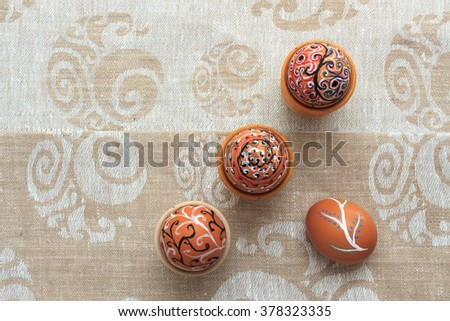 Handmade colorful painted easter eggs composition against matching tablecloth, top view with copy space. Easter greeting card concept - stock photo