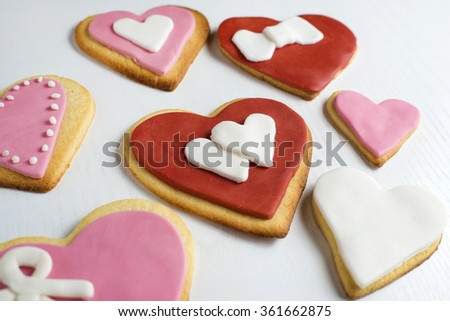 Handmade cookies with heart shape on white wood.