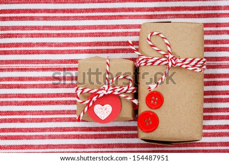 Handmade craft gift boxes on striped cloth - stock photo