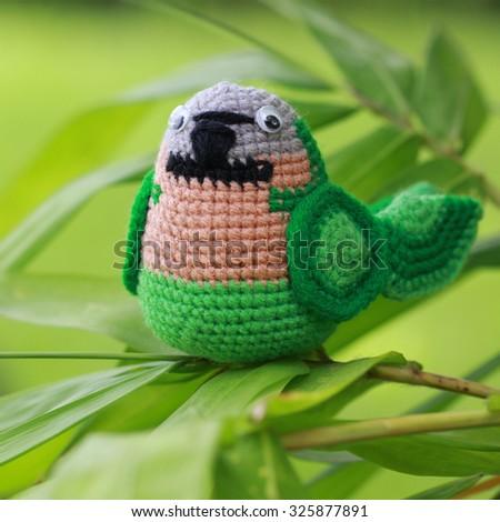 handmade crochet doll parrot on green background - stock photo