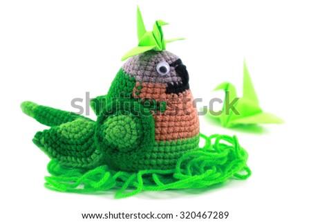 handmade crochet doll parrot on white background - stock photo