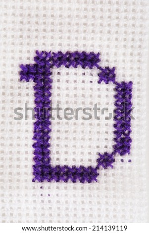 Handmade embroidered letter on white fabric background - stock photo